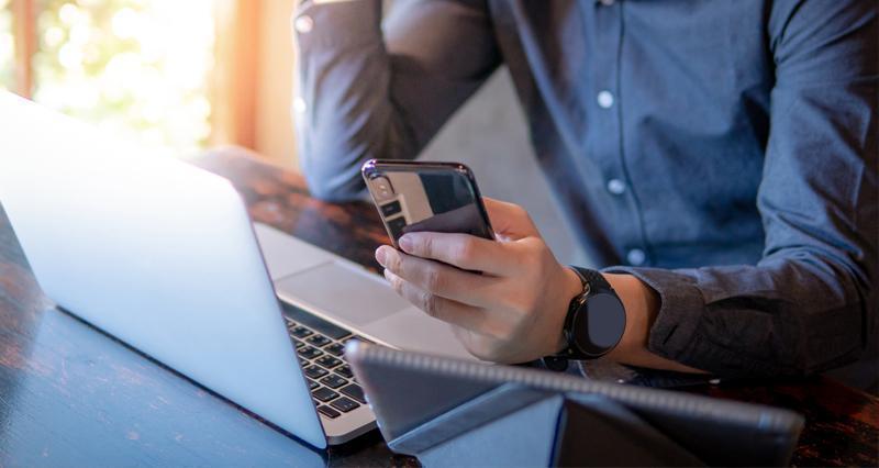Mężczyzna ztelefonem przy laptopie